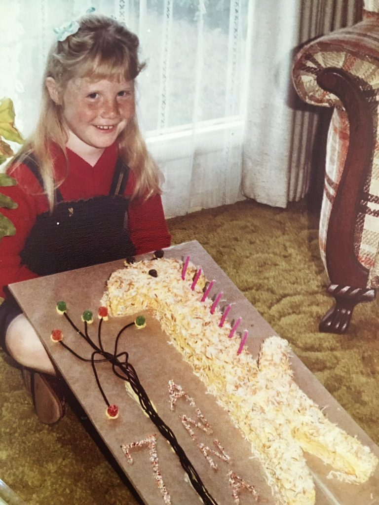 Anna holding her birthday cake in the shape of a giraffe on her 7th birthday.