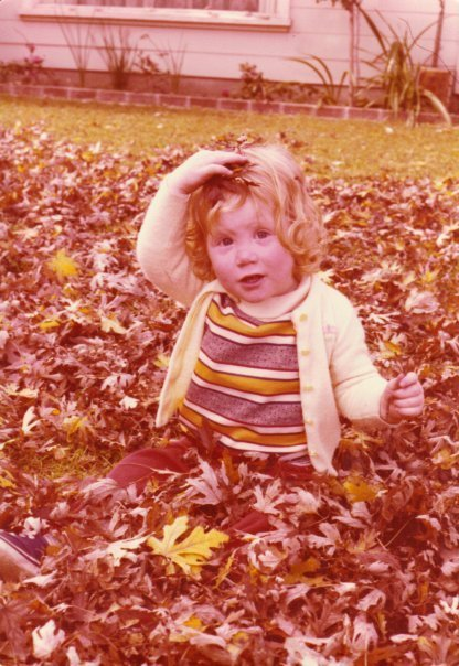 Anna as little girl, playing in the fall leaves