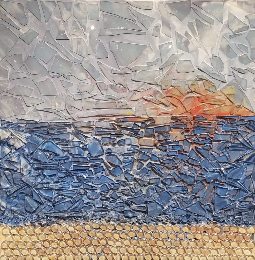 Seascape with a setting sun in the distance. Mixed media in acrylic and glass. A gray sky is in the back with an orange sunset. In the middle is a blue calm ocean. At the base is sand with round glass stones. Original artwork by Anna Loscotoff.