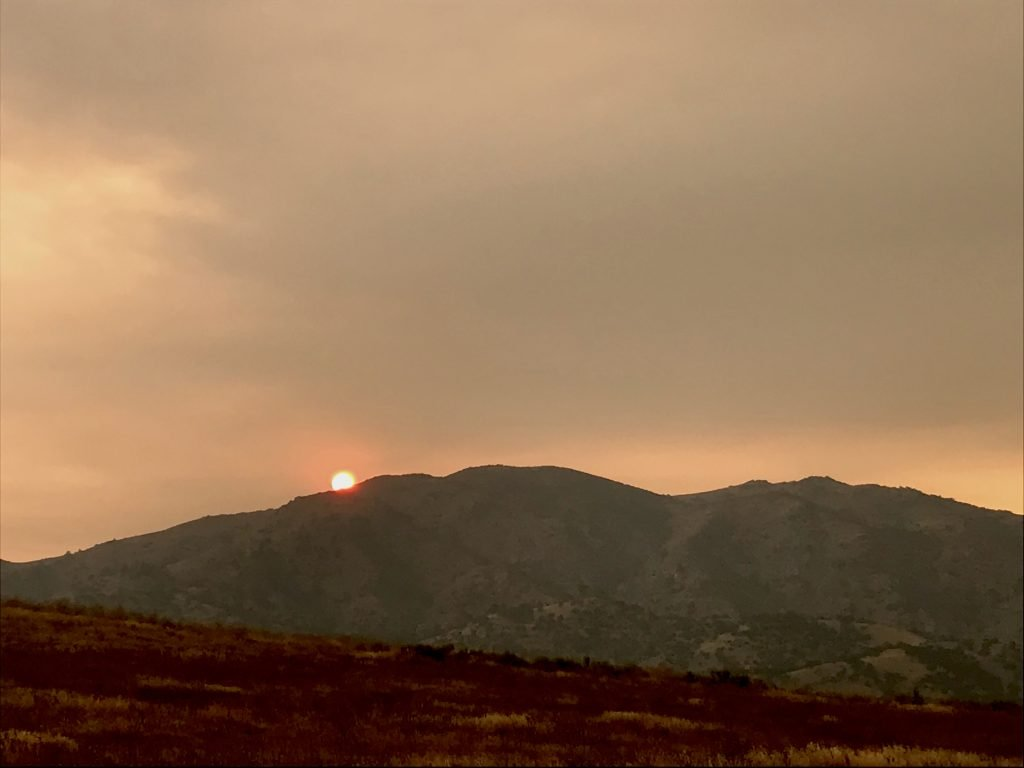 The sun is a small red ball disappearing past a hill, surrounded by California wildfire smoke.  The landscape looks red.