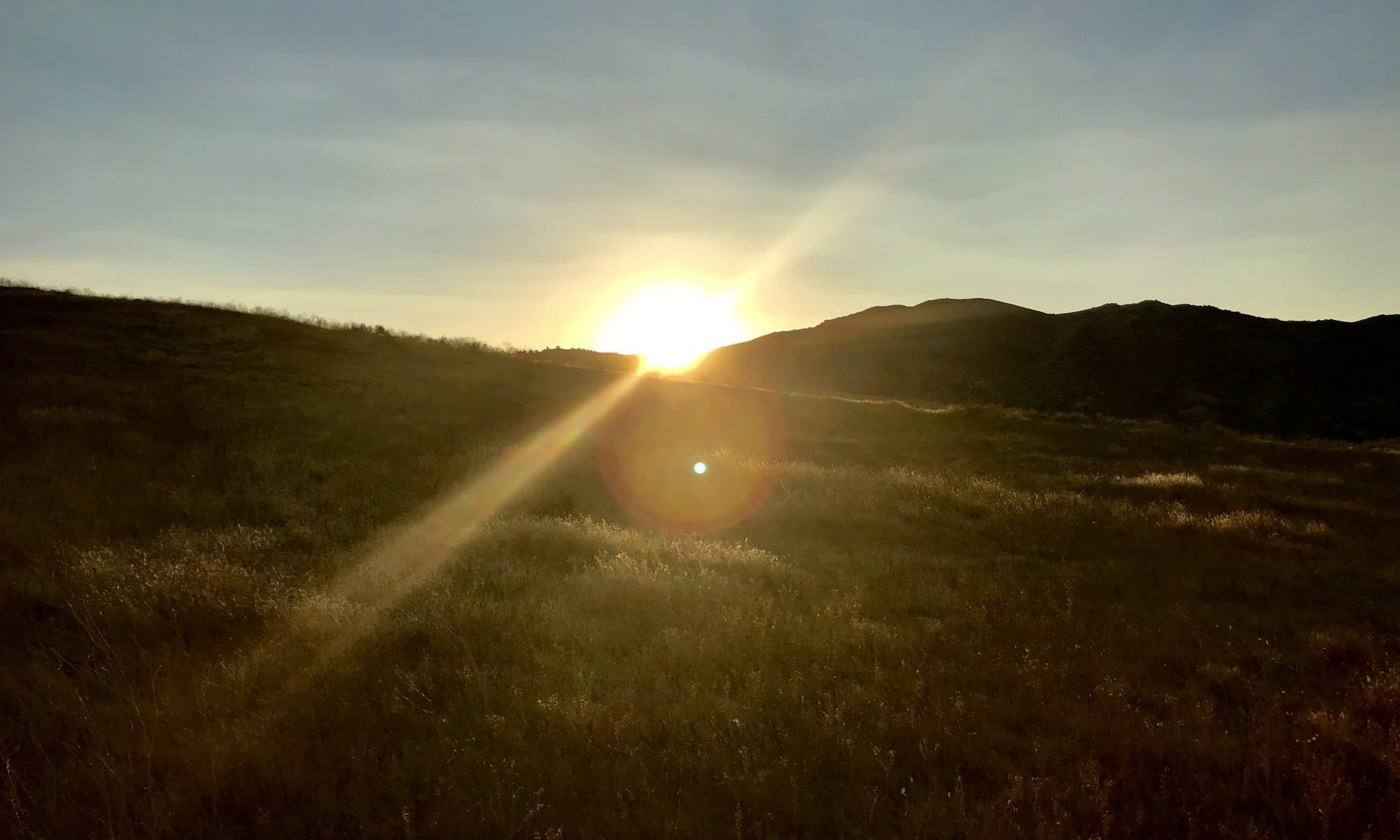 The rays of a sun shine out to the upper right and lower left as it sets behind a hill