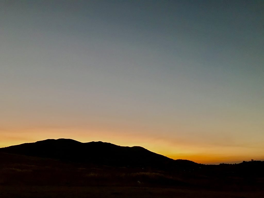A yellow and orange light around the Tehachapi Mountains after the sun has set