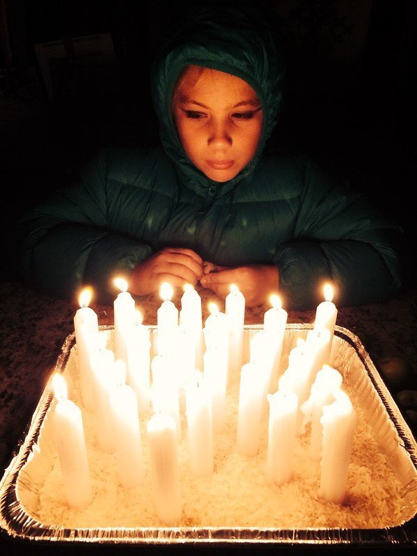 A girl stands, her face lit by many white candles honoring her ancestors. Photo by Anna Loscotoff.