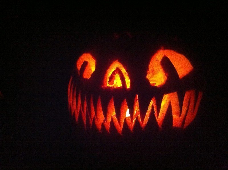 The lit up face of a jack-o'-lantern at night.  It has many sharp teeth and cat-like eyes.  Photo by Anna Loscotoff.
