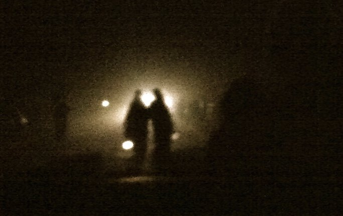 Two shapes move through the dark, silhouetted by a light in the distance. They carry a lantern. Photo by Anna Loscotoff.